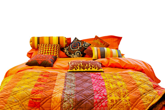 Big bed with colourful blanket and pillows